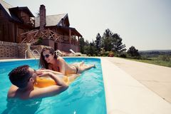 Beautiful couple in love enjoying summer resort. Beautiful couple in love enjoying themselves in pool at summer resort Stock Image