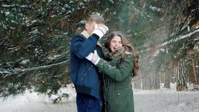 Beautiful couple in love in the forest in winter, snow flying on the head guy and girl are hugging, happy young people stock video