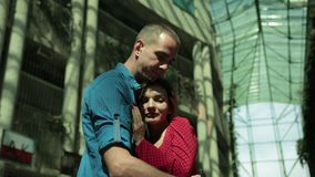 Girl and man tenderly embrace, next to an overgrown house with bushes. Beautiful couple in love, girl in red dress and man in blue shirt, tenderly embrace, next stock footage