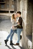 Beautiful couple in love kissing on street alley celebrating Valentines day. Candid portrait of beautiful European couple with rose in love kissing on street Stock Photography