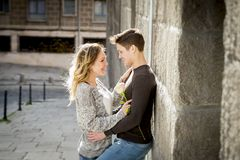 Beautiful couple in love kissing on street alley celebrating Valentines day. Candid portrait of beautiful European couple with rose in love kissing on street Stock Photo