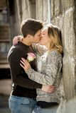 Beautiful couple in love kissing on street alley celebrating Valentines day. Candid portrait of beautiful European couple with rose in love kissing on street Royalty Free Stock Photography