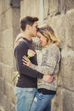 Beautiful couple in love kissing on street alley celebrating Valentines day. Candid portrait of beautiful European couple with rose in love kissing on street Royalty Free Stock Image