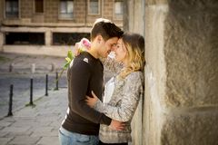 Beautiful couple in love kissing on street alley celebrating Valentines day. Candid portrait of beautiful European couple with rose in love kissing on street Stock Image