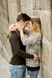 Beautiful couple in love kissing on street alley celebrating Valentines day. Candid romance portrait of beautiful European couple with rose in love kissing on Stock Images
