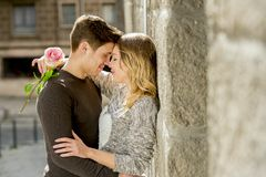 Beautiful couple in love kissing on street alley celebrating Valentines day. Candid romance portrait of beautiful European couple with rose in love kissing on Stock Photo