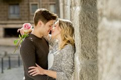 Beautiful couple in love kissing on street alley celebrating Valentines day. Candid romance portrait of beautiful European couple with rose in love kissing on Royalty Free Stock Images