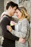 Beautiful couple in love kissing on street alley celebrating Valentines day. Candid and romantic portrait of beautiful European couple with rose in love kissing Royalty Free Stock Image