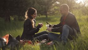 A guy and a girl in leather jackets on a date. Picnic in a pine grove. Biker on a date stock video footage