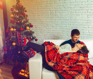 Beautiful couple in love lies on a couch wrapped in plaid Christ Stock Photo