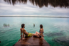 Beautiful couple in love looking at tranquil Bacalar lake royalty free stock photos