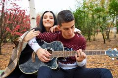 Beautiful couple in love on nature with a guitar stock image