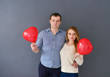 Beautiful couple in love with red balloon heart shape for valentine's day, on gray background Royalty Free Stock Photo
