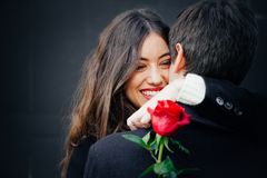 Beautiful couple in love with a rose. Beautiful and happy young women in love hugging her boyfriend holding a red rose Stock Photos