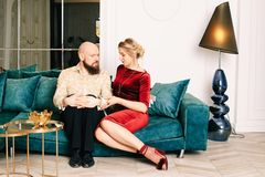 Beautiful couple in love sitting on the couch. In his beautiful bright house royalty free stock photo