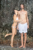 Beautiful couple in love standing under the water drops Royalty Free Stock Photography