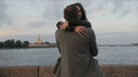 Beautiful couple in love swirling around, smiling, kissing The Peter and Paul Fortress, river at the background, slow mo stock footage