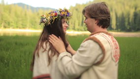 Beautiful couple in love in traditional ukrainian clothes kissing  at the green field. Handsome young man puts on woman stock footage