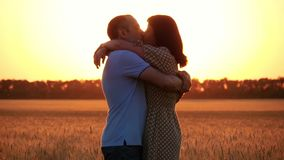 A beautiful couple in love in a wheat field at sunset. The woman runs to the man kisses and embraces him. Happy family