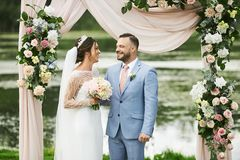 A beautiful couple of lovers near the wedding arch, decorated with fresh flowers, a young beautiful woman in the wedding royalty free stock photography