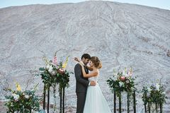 A beautiful couple of lovers at a white desert, a young woman with a wedding hairstyle in a stylish dress and handsome royalty free stock photo