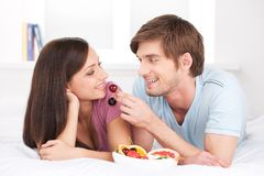 Beautiful couple lying in bed and eating. Stock Images