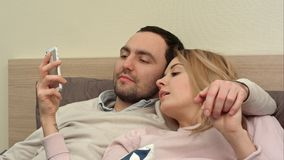 Beautiful couple lying on bed and use smartphone, taking panorama photo stock image