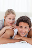 Beautiful couple lying dowon their bed Stock Images