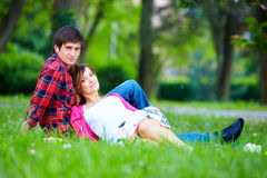 Beautiful couple lying on green grass Royalty Free Stock Image