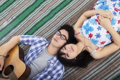 Beautiful couple lying on mat with guitar Royalty Free Stock Photos