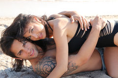 Beautiful couple lying on the sand Royalty Free Stock Photos