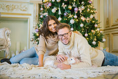 Beautiful couple lying under the Christmas tree stock photos