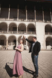 Beautiful couple, man, girl with long pink dress posing in old castle near columns. Krakow Vavel Stock Images