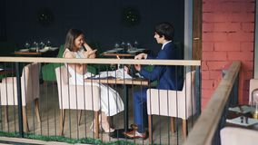 Beautiful couple man and woman are enjoying date in restaurant when guy is making marriage proposal to girl, giving her. Beautiful happy couple man and woman are stock video footage