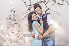 Beautiful couple man and woman hugging in the Christmas interior Stock Photography