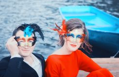 Beautiful Couple In Masquerade Masks. Colorful portrait of a young couple in masquerade masks - elegantly dressed men and women against the boat on the water royalty free stock image