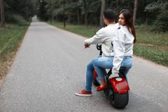 Beautiful couple man and woman ride on a modern electric bike. Beautiful couple men and women ride on a modern electric bike in the park stock photo