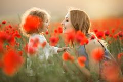 Beautiful smiling child girl with young mother are having fun in field of poppy flowers over sunset lights. Beautiful couple mother and cute daughter are walking stock photography