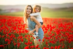 Beautiful smiling child girl with young mother are having fun in field of poppy flowers over sunset lights. Beautiful couple mother and cute daughter are walking royalty free stock photography