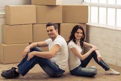 Beautiful couple moving. Attractive young couple is moving, looking at camera and smiling while sitting back to back with cardboard boxes in the background Stock Photos