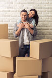 Beautiful couple moving. Happy young couple is moving, cuddling, looking at camera and smiling while standing among cardboard boxes. Woman is pickaback Royalty Free Stock Photos