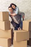 Beautiful couple moving. Happy young couple is moving, cuddling, looking at camera and smiling while standing among cardboard boxes. Woman is pickaback Stock Photography