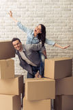 Beautiful couple moving. Happy young couple is moving, cuddling, looking at camera and smiling while standing among cardboard boxes. Woman is pickaback Royalty Free Stock Photography