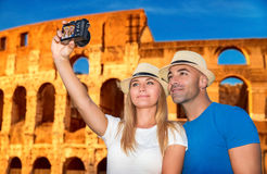 Beautiful couple near Coliseum. Beautiful couple taking picture of them self on Coliseum background, happy young family spending summer vacation in Rome, Italy royalty free stock photos