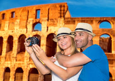 Beautiful couple near the Coliseum. Beautiful couple taking picture of themself on Coliseum background, happy young family spending summer vacation in Rome royalty free stock images