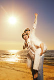 Beautiful couple near the sea. Handsome young man giving his girlfriend piggyback ride near the ocean at sunset Stock Images
