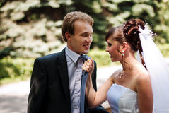 Beautiful couple newlywed. Beautiful and young married couple in the park, wife caught her husband for a tie royalty free stock images