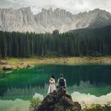 Beautiful stylish bride and groom walking in summer alpine meado stock image