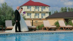 Beautiful Couple of Newlyweds Walking Near Pool stock video