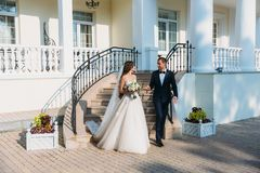 Beautiful couple of newlyweds walking in a park with a beautiful white building. Young groom in a black suit and bride. With long hair in a wedding dress Royalty Free Stock Images